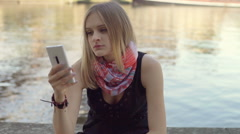 Tired woman sitting next to the water and browsing internet on smartphone Stock Footage