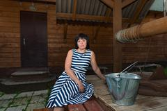 Middle-aged brunette woman standing at the village well with a wooden bucket Stock Photos