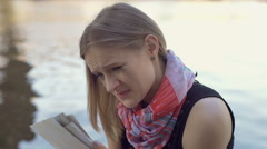 Sad girl crying while reading love letter next to the river Stock Footage