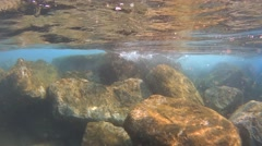 Waves splashing under water over the rocks, slow motion Stock Footage