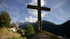 Motion timelapse of an alpine village and a christian cross Stock Footage