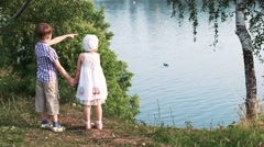 2 kids standing near the river outside Stock Footage