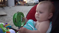 Baby girl playing rattle in her stroller - summer day Stock Footage