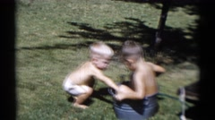 1959: young boy sitting in a tin pail splashes cup filled with water on toddler Stock Footage