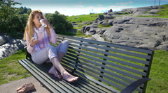 A young woman uses a smartphone and drinks coffee on a bench in a city park. Stock Footage
