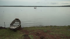 A beached boat on shore and fishermen on a lake in Mali, Africa. Stock Footage