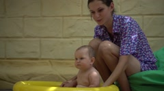 Mom bathes water small child in inflatable pool Stock Footage