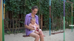 Mom keeps a small child in her arms swinging on a swing Stock Footage