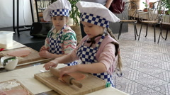 Two little girls dressed in uniforms chef learning to roll out the dough with a Stock Footage