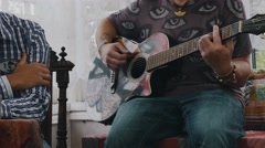 Bearded man listen man play guitar at table with alcohol drinks. Country house Stock Footage