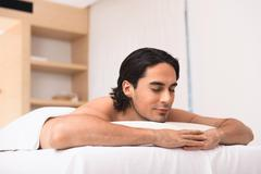 Amicable man dreaming in spa salon Stock Photos