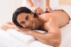 Happy guy enjoying treatment by masseuse Stock Photos