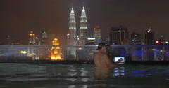 Woman with pad on rooftop pool in Kuala Lumpur, Malaysia Stock Footage