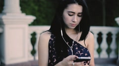 Young adult woman listening music on smartphone through earphones Stock Footage