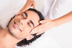 Skillful masseuse doing facial massage Kuvituskuvat