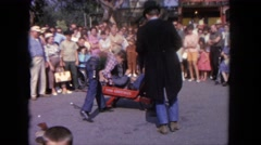 1962: a person is seen curing a person who seems to be fainted and the crowd Stock Footage