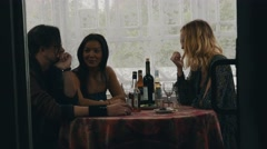 Two girls and man chat at table with drinks on terrace of country house Stock Footage