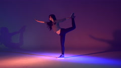Silhouette of young Asian American female dancer stretching in studio Stock Footage