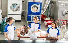 Smiling worker adds ironed linens Stock Photos