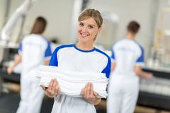 Smiling employed holding clean and ironing textiles Stock Photos