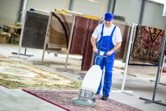 Worker cleaning with vacuum cleaner Stock Photos
