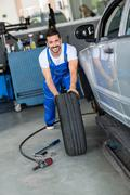 Smiling mechanic repair and  pushing a black tyre Stock Photos