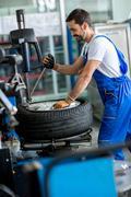 Mechanic repairman balancing  car wheel Stock Photos