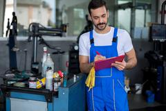 Concentrated mechanic writing on clipboard Stock Photos