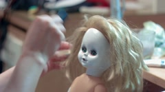 Young woman brushing doll har Stock Footage