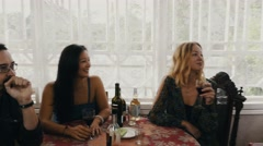 Friends drink wine at table on terrace of country house. Man knock at window Stock Footage