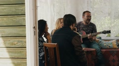 Company of friends relax at table on terrace of country house. Man play guitar Stock Footage