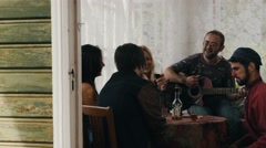 Friends in country house. Man play guitar. Man with red nose drink cognac Stock Footage