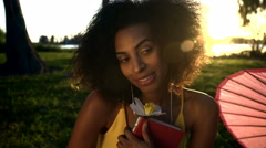 Cute African American female listening music on Summer vacation in park Stock Footage