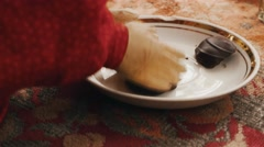 Toy doll take big chocolate candy from plate by wooden hands. Entertainment Stock Footage