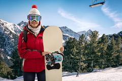 Smiling woman in snowy mountains, extreme sport and winter holiday Stock Photos