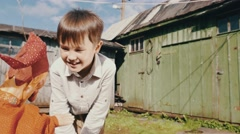 Toy doll in orange costume play with boy on street in countryside. Puppet show Stock Footage