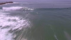 Surfer catching wave in surf beach, aerial shot Stock Footage