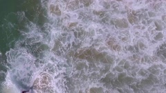 Aerial shot, overhead surfer catching wave in beach Stock Footage