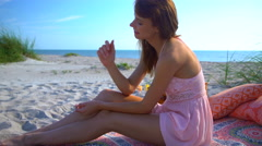Happy cute Caucasian American woman enjoying picnic on Summer holiday beach Stock Footage
