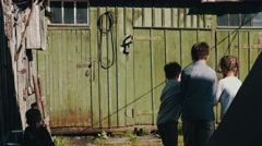 Children playing on street in countryside. Close girl in old green barn. Game Stock Footage