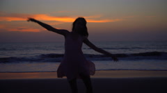 Silhouette of Caucasian American female dancing on beach on vacation at sunrise Stock Footage