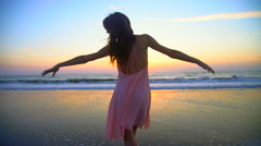 Silhouette of Caucasian American woman dancing on beach on holiday at sunrise Stock Footage