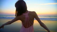 Silhouette of cute Caucasian American woman enjoying sunrise on ocean beach Stock Footage