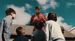 Man in red shirt give out children rooster lollipop on street in countryside Stock Footage