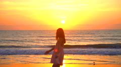 Slim Caucasian American woman posing on sea coast at sunset Stock Footage