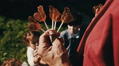 Man give out children rooster lollipop on street in countryside. Summer day Stock Footage