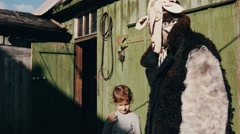 Man in creepy costume take hand of girl at old barn in countryside. Sunny day Stock Footage