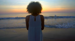 Silhouette of African American woman dancing on beach on vacation at sunrise Stock Footage