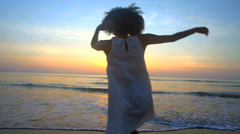 Silhouette of slim African American female dancing on sea coast at sunset Stock Footage