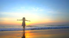 Silhouette of ethnic female dancing on beach on holiday at sunrise Stock Footage